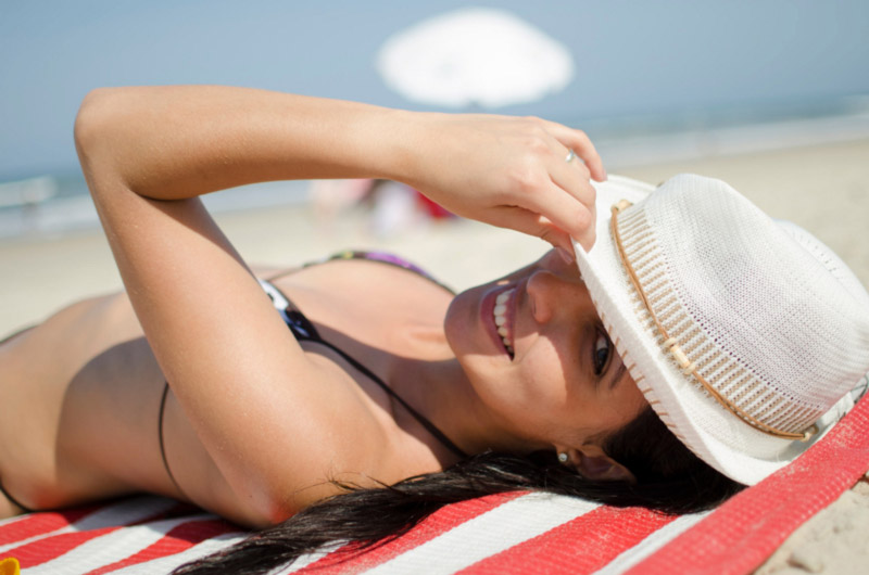 women with hat on the beach hair care