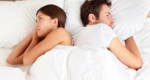 couple try to sleep in bed