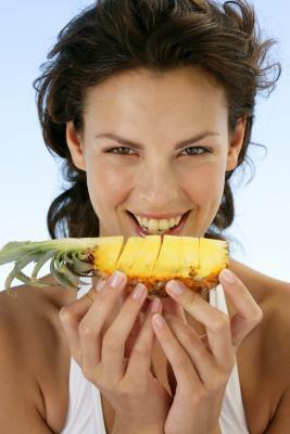 women eating pineapple